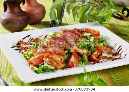 Still salad with chicken nuggets, arugula, bacon, tomatoes, balsamic sauce on a wooden table green menu
