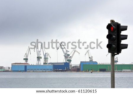 Still stand in ship industry with stoplight as symbol and dark clouds - stock photo