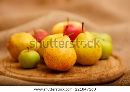 Still, the composition of different kinds of apples and pears. Autumn harvest fruit piled on a table. Apples of various colors, red, green, yellow. Ripe fruit on the table next to each other. autumn - stock photo