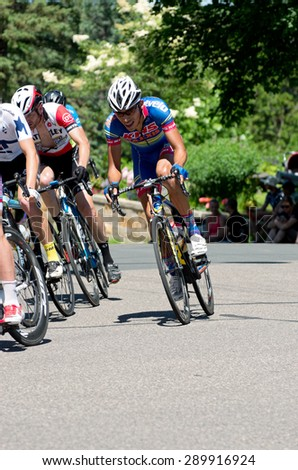 STILLWATER, MN/USA - JUNE 21, 2015: Cyclist races toward front of peloton at Stillwater Criterium or stage six of prestigious 2015 North Star Grand Prix pro cycling event in Stillwater.  - stock photo