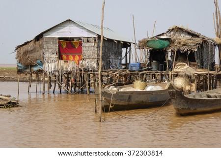 Stilt houses during dry season at the Kompong Kleang floating fishing village,  Cambodia - stock photo