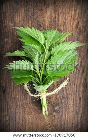 stinging nettle on a wooden background  - stock photo