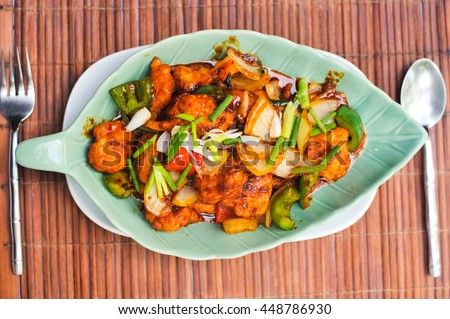 Stir fried chicken mix cashew nut Thai vegetable fruit and herb on beautiful dish with spoon fork.