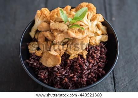 Stir-fried chicken with cauliflower and riceberry rice - stock photo