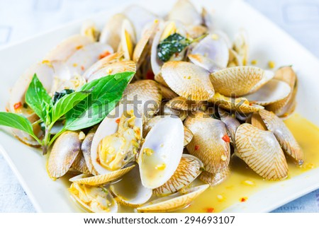 Stir fried clams with roasted chili paste on white dish and white background.Thai food