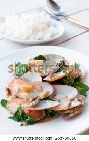 stir fried clams with roasted chili paste on wooden board, Thai food