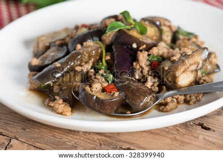 Stir fried eggplant with minced pork and basil in white plate. selective focus. - stock photo