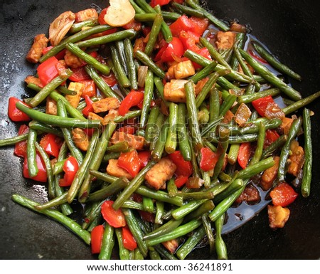 Stir fried green beans with red pepper, ginger and tempeh in black wok, tumis boentjes - stock photo