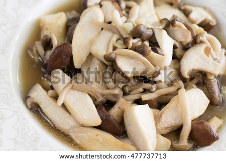 Stir fried mushroom in white dish on brown napery / Selective focus