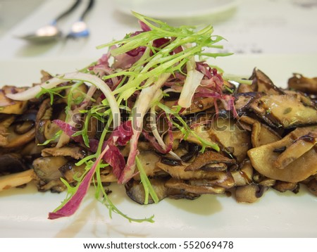 Stir-fried mushrooms on a white plate.