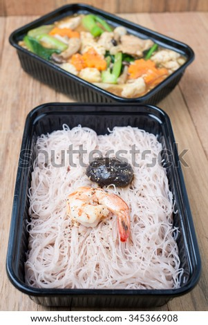 stir-fried noodles with  pork and prawns in plastic box on wooden table,very healthy food,Slimming concept.