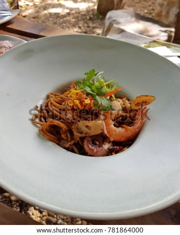 Stir fried noodles with spicy seafood sauce in Thai style served on white plate.