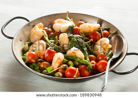 Stir-fried of Shrimps, green asparagus, capers, spring onion and peppermint in old pan - stock photo