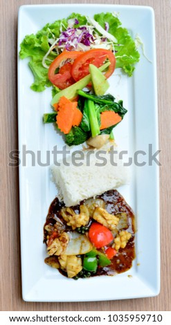 Stir-Fried squid with vegetable and rice in white plate on brown wood background, Thailand cuisine, Thai food