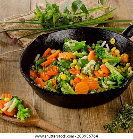 Stir fried vegetables in  iron skillet . Selective focus - stock photo