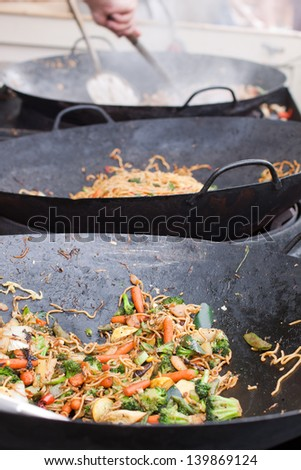 Stir Fried Vegetables in Wok at Open-Air Festival - stock photo