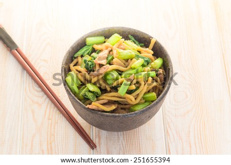 stir-fried yellow noodles with pork on wood table