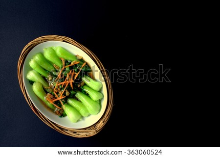 Stir Fry Bok Choy chinese vegetables, with oyster sauce and garlic. garnish with shredded carrot on black back ground - stock photo