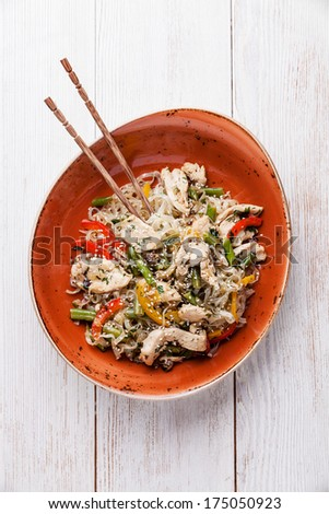 Stir fry chicken with vegetables and rice noodles on red plate