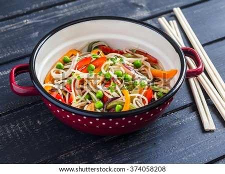 Stir fry vegetable with rice noodles in an enamel pot on dark wooden background - stock photo