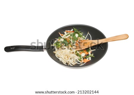 Stir fry vegetables and bean sprouts in a wok with a wooden spatula isolated against white