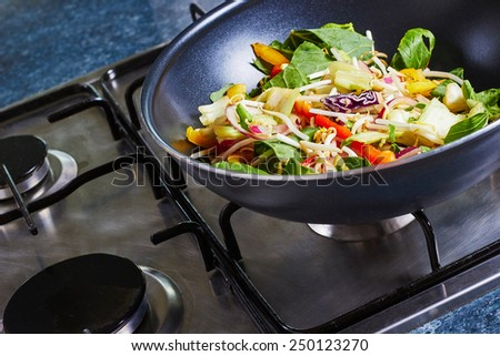 Stir fry vegetables in a wok cooking on the stove - stock photo
