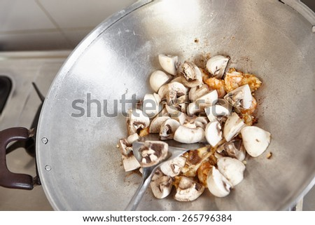 Stir frying the mushroom on the wok - stock photo