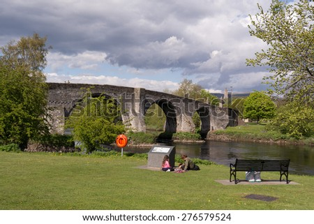 STIRLING, SCOTLAND, UK - 9 MAY 2015: enjoying a warm spring day by Stirling Old Bridge, which crosses the River Forth close to where the wooden bridge of the Battle of Stirling Bridge would have stood - stock photo