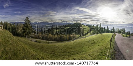 Stitched wide-angle panorama of green Alpine hills with forests and mountains on the background. Sunny holiday. Plane traces in the sky