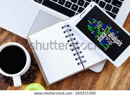 Stock Analysis word cloud arrangement concept on smartphone. Notebook,smartphone, book and a cup of coffee on wooden table. - stock photo