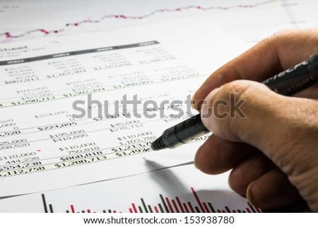 stock chart report with hand of someone