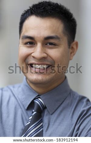 Stock closeup headshot photo of a smiling Hispanic businessman. - stock photo