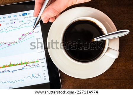 Stock Data Analysis for coffee cup, mark the pen by hand - stock photo