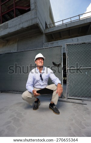 Stock image construction contractor squatting by a construction site - stock photo