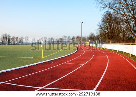 Stock image of a football field with running track in the evening, signifying concept of dreams and aspirations - stock photo