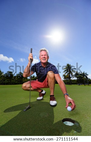 Stock image of a golfer taking out the ball from the hole - stock photo