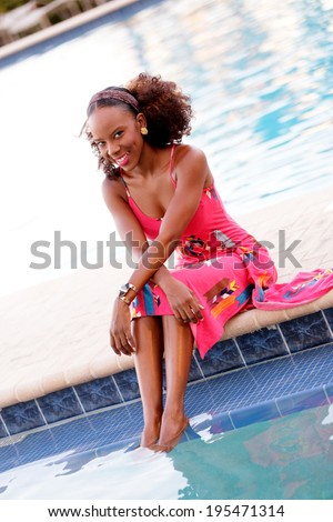 Stock image of a Jamaican woman sitting by the pool in her dress - stock photo