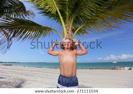 Stock image of a man flexing his arm muscles on the beach - stock photo