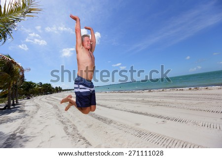 Stock image of a man jumping on the beach - stock photo