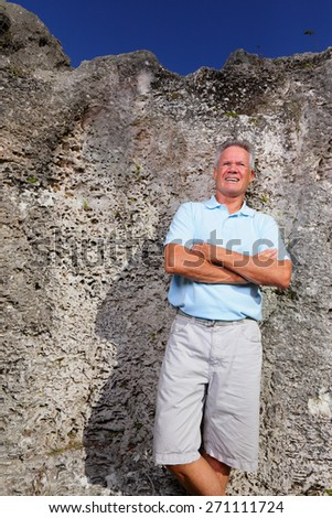 Stock image of a man posing by a rock wall with arms crossed - stock photo