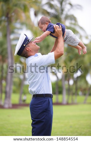 Stock image of a man raising his baby in the air - stock photo