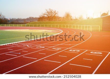 Stock image of a running track in an evening sunset signifying concept of dreams and aspirations - stock photo