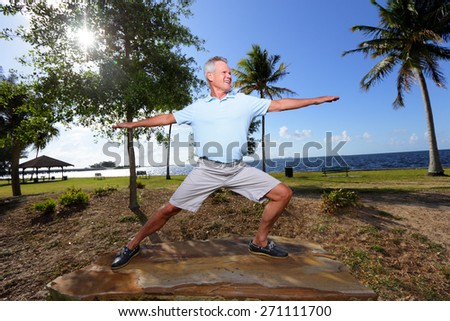 Stock image of a senior man doing yoga in the park - stock photo