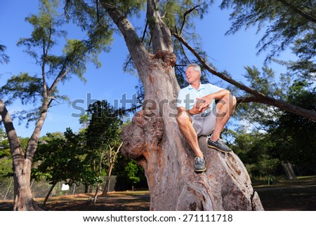 Stock image of a senior man sitting on a tree in the park - stock photo