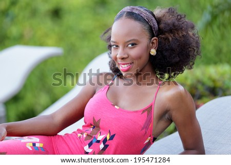 Stock image of a young Jamaican woman posing on a lounge chair by the pool - stock photo