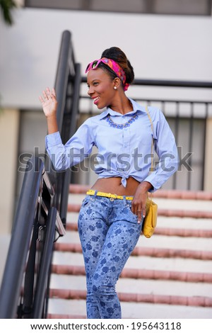 Stock image of a young Jamaican woman waving and smiling on a staircase - stock photo