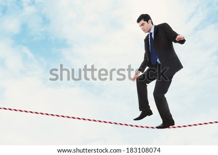 Stock image of businessman walking the tightrope - stock photo