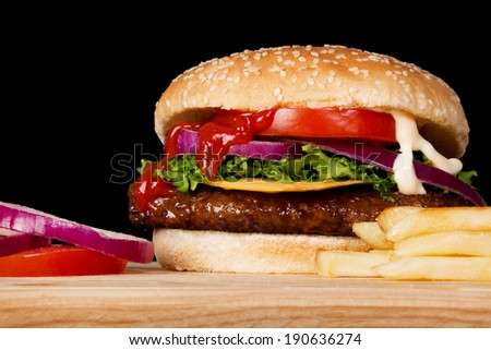 Stock image of cheeseburger with fries on wooden plate - stock photo