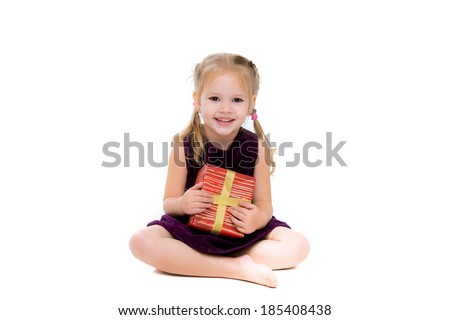 Stock image of cute little girl sitting with present and smiling, isolated on white with shadow on floor - stock photo