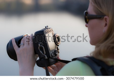 Stock image of girl checking her DSLR camera. Photography workshop concept